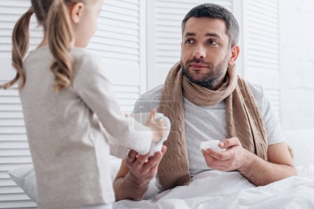 daughter giving cup of tea to sick father in bedroom