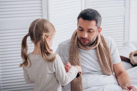 Photo pour Verser les médicaments dans une cuillère pour papa malade dans la chambre de fille - image libre de droit