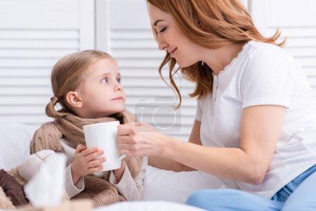 Photo pour Mère prendre soin de sa fille malade et donner sa tasse de thé dans la chambre - image libre de droit