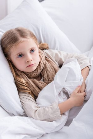 sick child with scarf over neck lying in bed at home and looking away