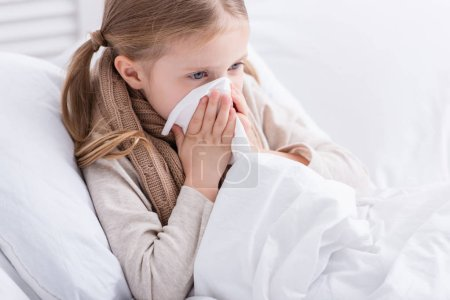 sick child with scarf over neck lying in bed and blowing nose in tissue at home