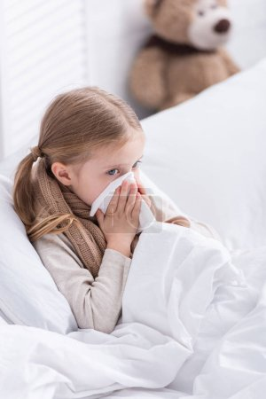 sick kid with scarf over neck lying in bed and blowing nose in tissue at home