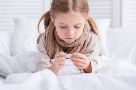 sick child with scarf over neck lying in bed and looking at thermometer at home