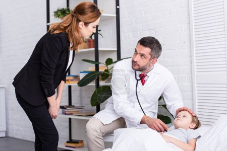 pediatrist in white coat examining sick boy with stethoscope and looking at mother