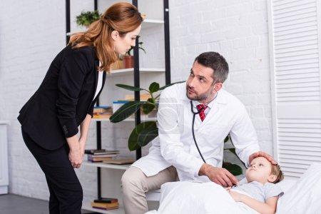 pédiatre en manteau blanc examinant garçon malade avec stéthoscope et regardant mère
