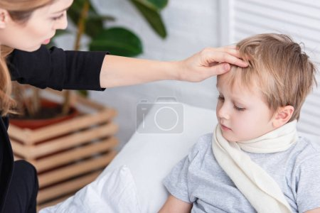 mother taking care of sick son and touching his forehead in bedroom