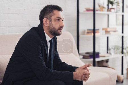 Photo for Side view of worried handsome businessman in suit sitting on sofa in office and looking away - Royalty Free Image