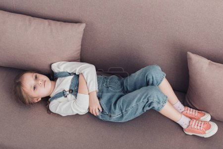 high angle view of sick child with stomach pain lying on sofa in living room
