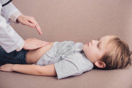Photo pour Image recadrée d'un pédiatre palpant l'estomac d'un garçon malade sur un canapé dans le salon - image libre de droit