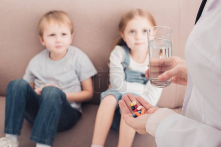 Photo for Cropped image of pediatrist holding pills and glass of water for sick children in living room - Royalty Free Image