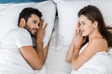 top view of young couple lying in bed and looking at each other
