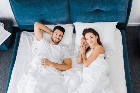 Photo pour Vue de dessus de jeune couple souriant couché dans le lit ensemble - image libre de droit