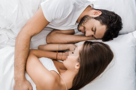 jeune couple dort et des caresses dans le lit blanc