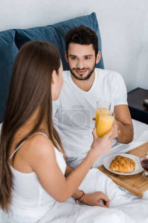 Photo for Handsome man looking at girlfriend and clinking with glasses of orange juice - Royalty Free Image