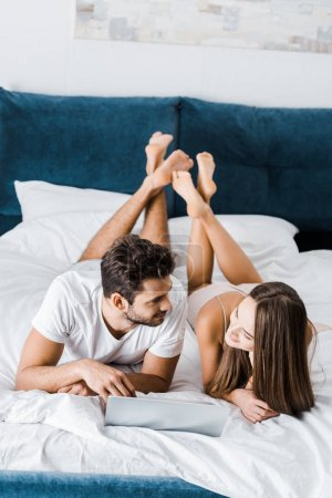 Photo for Young couple lying in bed with crossed legs and laptop while looking at each other - Royalty Free Image