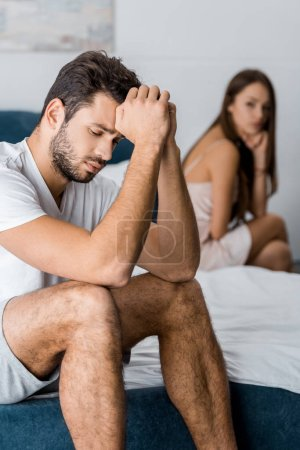 upset man with hands near head sitting on bed with girlfriend after quarrel, sexual problems concept