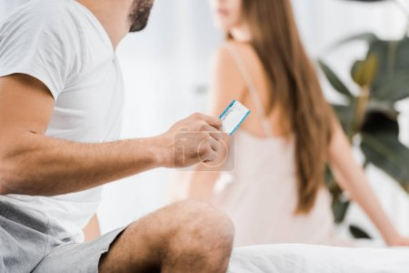 cropped view of young man holding condom and looking at girlfriend