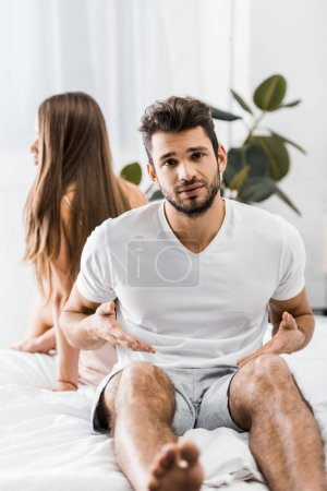 young dissatisfied man having sexual problems while sitting on bed next to girlfriend