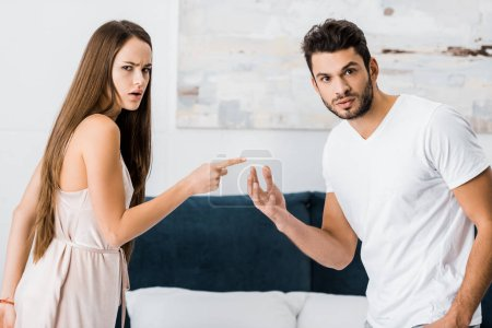 young attractive woman pointing with finger angrily at man