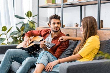 Foto de Hombre guapo joven sentado en el sofá en la sala de estar y tocar la guitarra acústica para novia - Imagen libre de derechos