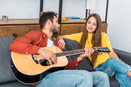 young couple sitting on sofa and looking at each other while man playing guitar