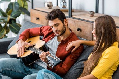 Photo pour Jeune fille assise sur le canapé avec petit ami tout en écoutant de la musique de guitare - image libre de droit