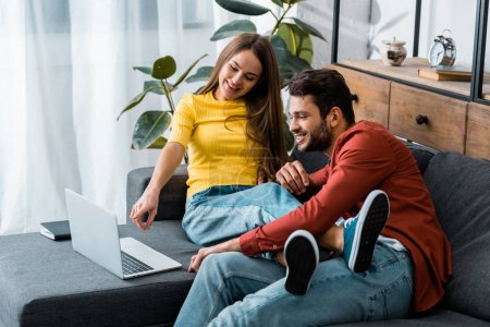 young couple sitting on sofa while girl pointing with finger at laptop