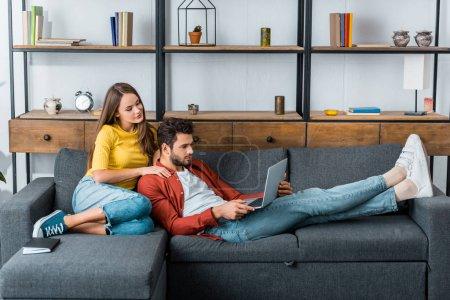 Photo pour Belle jeune femme étreignant l'homme qui à l'aide d'ordinateur portable - image libre de droit