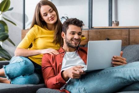 Photo for Young couple looking at laptop in living room - Royalty Free Image