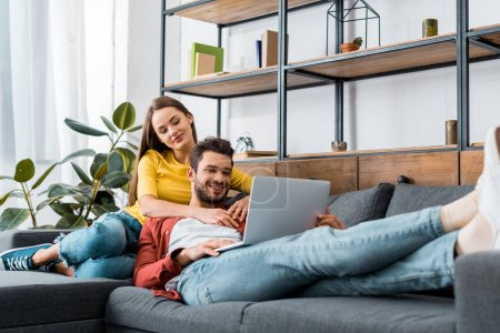 Photo for Young happy couple resting on sofa with laptop - Royalty Free Image