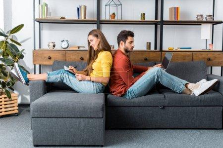 junge lächelnde Frau mit Notizbuch sitzt Rücken an Rücken auf dem Sofa mit Mann mit Laptop