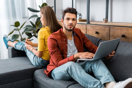 young man holding laptop and sitting back to back with woman on sofa