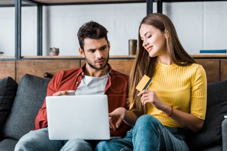 attractive woman holding credit card while boyfriend sitting with laptop