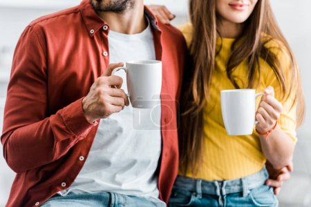 Photo for Cropped view of couple holding cups with drinks - Royalty Free Image