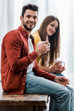 Photo for Selective focus of happy boyfriend and girlfriend holding cups in kitchen - Royalty Free Image