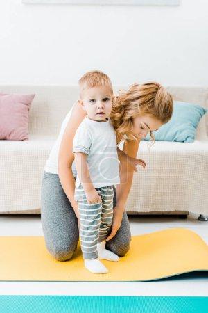 Photo pour Séduisant enfant femme et enfant en bas âge sur des nattes de fitness - image libre de droit