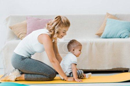 Photo pour Mère, assis sur des tapis de remise en forme et souriant derrière l'enfant enfant en bas âge - image libre de droit