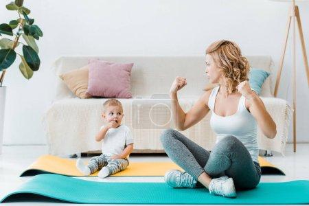 Mutter sitzt auf Fitnessmatten und schaut niedlichen Kleinkind-Sohn an