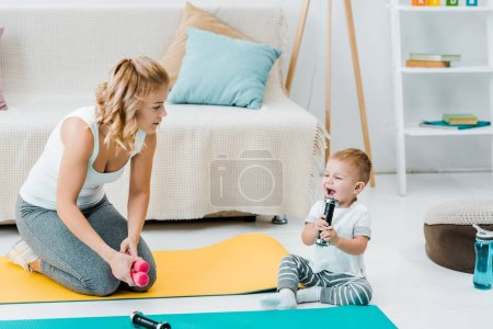 mother looking at adorable child son while boy smiling and lifting weights
