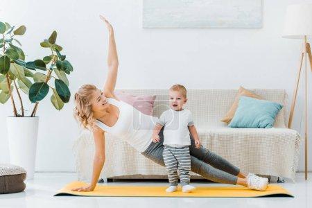 Photo pour Femme couchée sur le tapis fitness et souriant à garçon adorable - image libre de droit