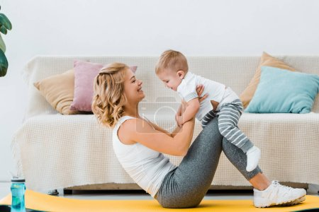 Photo pour Femme allongée sur le tapis de fitness tout en formation et enfant adorable tenue en mains - image libre de droit