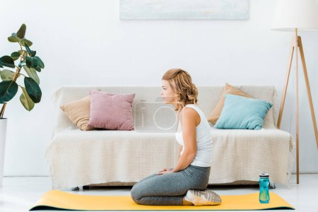 tired woman in sportswear on yellow fitness mat in living room