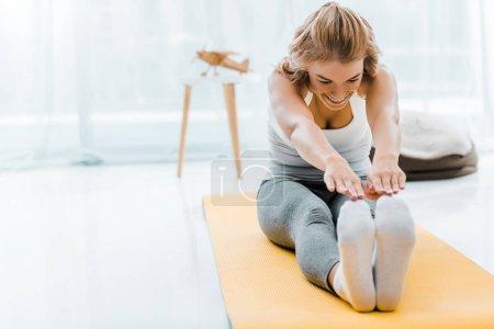 Photo pour Femme souriante, Sportswear, faire de l'exercice qui s'étend sur tapis de fitness dans la salle de séjour - image libre de droit