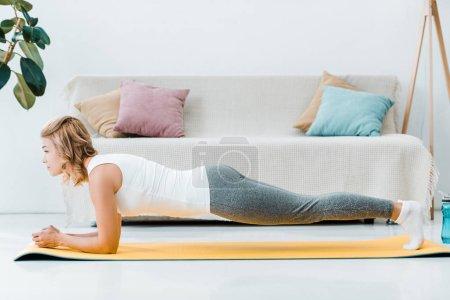 Photo pour Jolie femme sportswear faisant la planche sur le tapis de fitness jaune dans le salon - image libre de droit