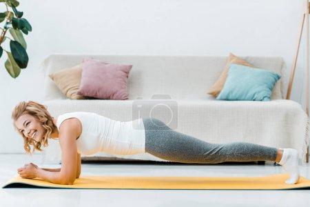 Photo pour Femme souriante, Sportswear, faire la planche sur le tapis de fitness jaune à la maison - image libre de droit