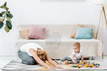 Foto de Mujer haciendo ejercicio que estira sobre alfombra y niño lindo muchacho jugando con cubos multicolores en sala de estar - Imagen libre de derechos