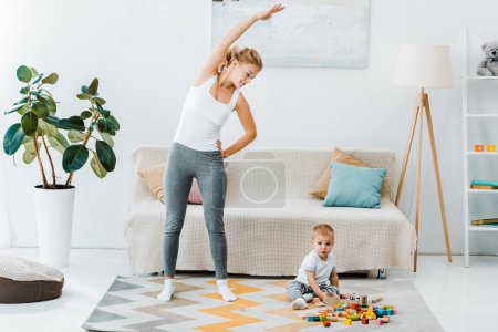 mother doing exercise and looking at cute toddler boy sitting on carpet and playing with multicolored cubes in living room