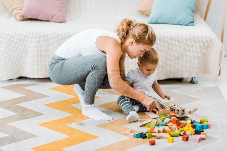 Foto de Mujer atractiva y niño lindo niño jugando con cubos de madera multicoloras alfombra en casa - Imagen libre de derechos
