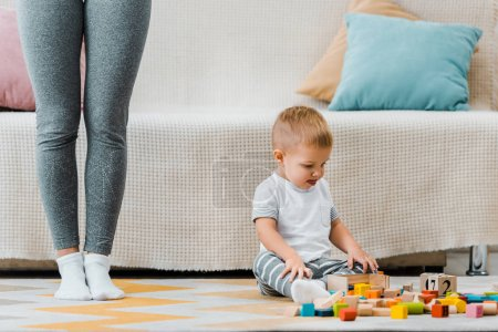 Photo for Cute toddler boy playing with multicolored cubes and sitting on carpet at mom legs - Royalty Free Image