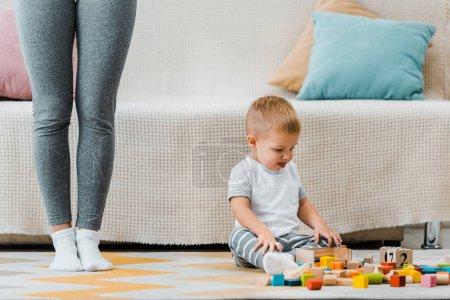 Foto de Chico lindo niño jugando con cubos multicolores y sentado en la alfombra en las piernas de mamá - Imagen libre de derechos